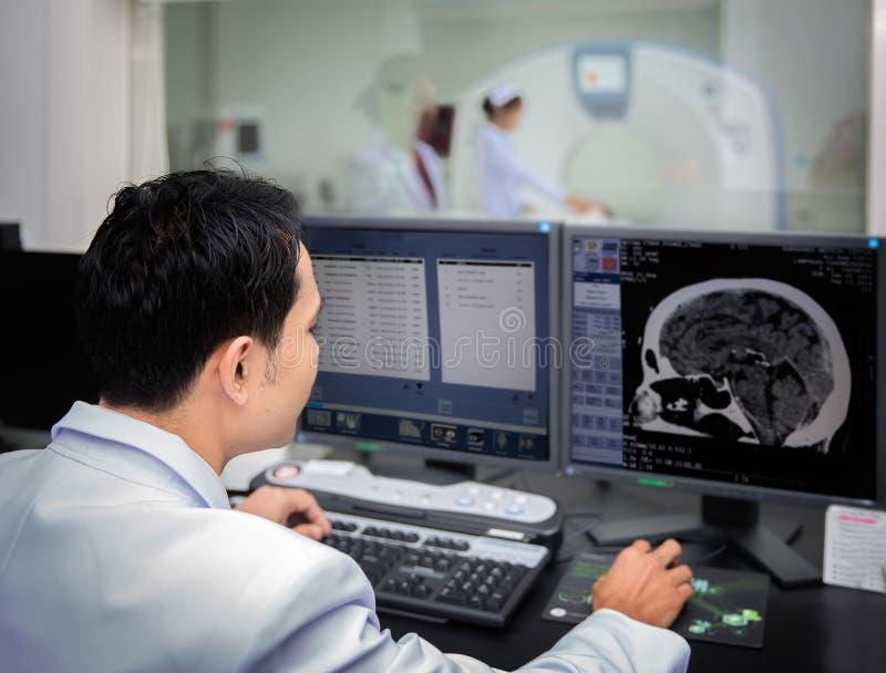 医疗队操作计算机在CT扫描实验室 免版税库存照片