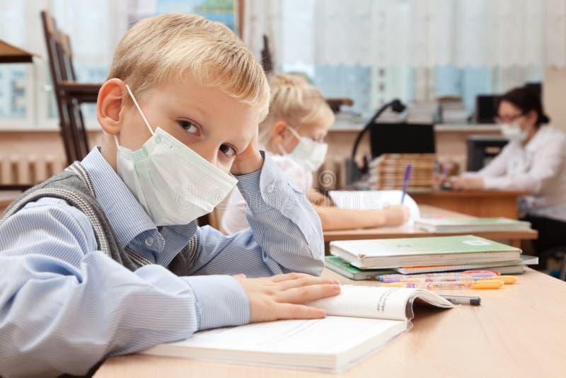 医疗面罩的小学生 库存照片