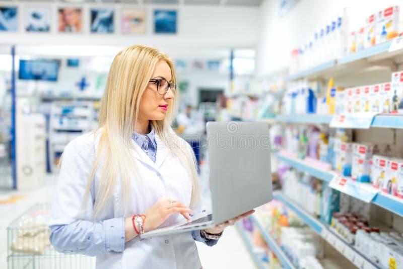 医疗领域的白肤金发的药剂师使用张贴的网上药物广告膝上型计算机和片剂技术 图库摄影
