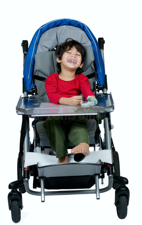 医疗婴儿推车的三岁的两种人种的残疾男孩,愉快 免版税库存图片