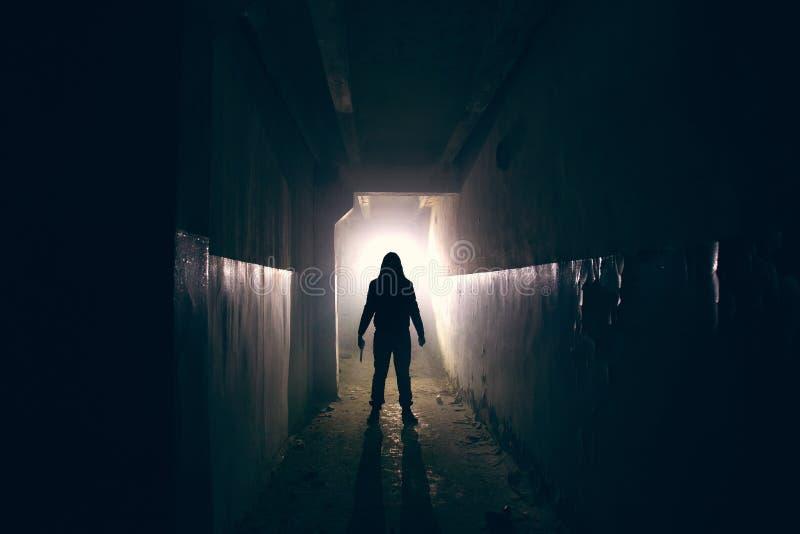 疯子剪影有刀子的在手中在长的黑暗的蠕动的走廊,恐怖精神分析的疯狂或者连环杀手概念 免版税库存图片