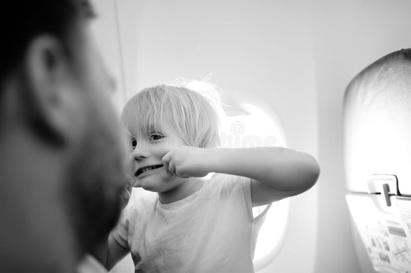 疯狂和傻的小男孩画象有他疲乏的父亲的在旅行乘飞机期间 免版税库存照片
