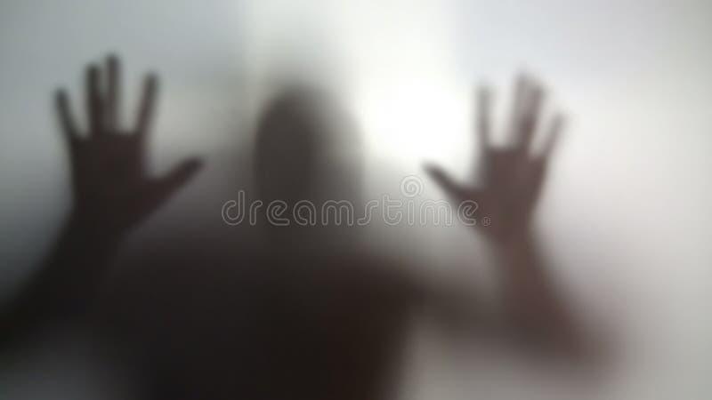 疯狂的人剪影对透明墙壁,精神分裂症,瘾 免版税图库摄影