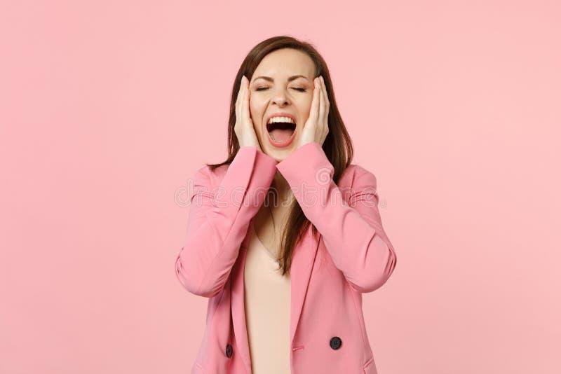 疯狂的叫喊的年轻女人画象保留眼睛的夹克的关闭了,把手放在粉红彩笔的面颊上 库存图片