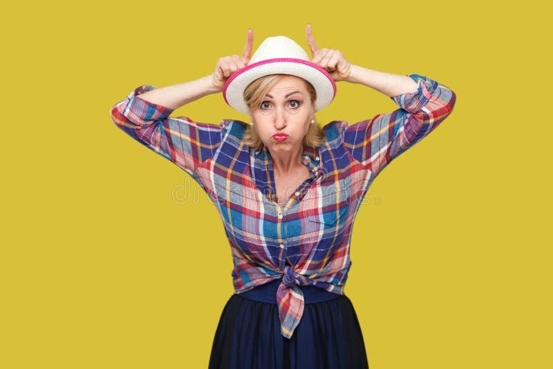 疯狂的可笑的现代时髦的成熟妇女画象便装样式的与与母牛垫铁的白色帽子身分在头用手和 库存图片