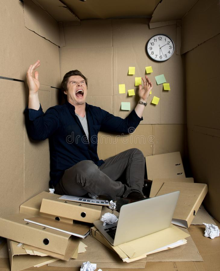 疯狂的商人表现出从他工作和叫喊的愤怒 库存图片