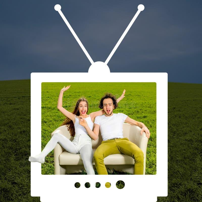 疯狂的夫妇坐在绿色领域的长沙发   免版税库存照片