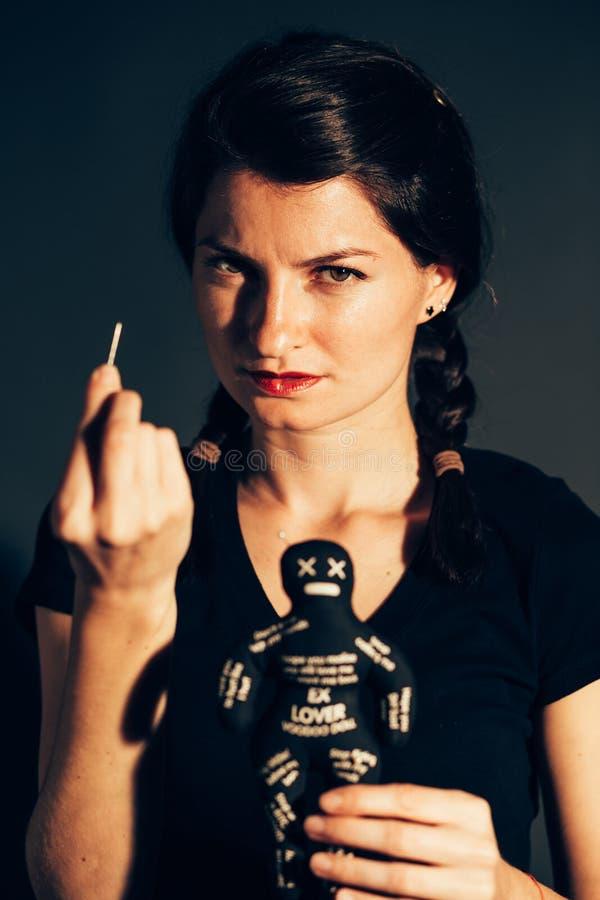 疯狂的妇女藏品伏都教玩偶 免版税图库摄影