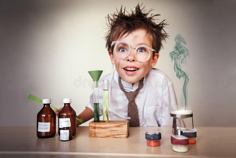 疯狂的科学家。执行实验的年轻男孩 免版税库存图片