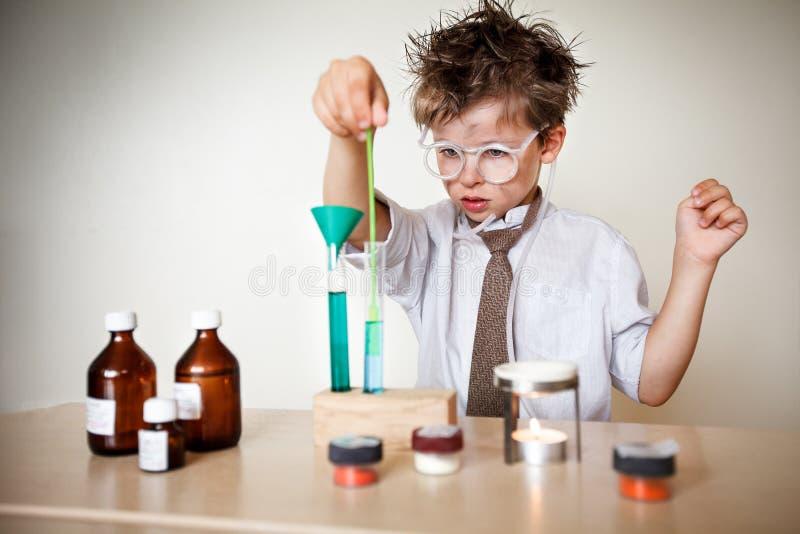 疯狂的科学家。执行实验的年轻男孩 免版税库存照片