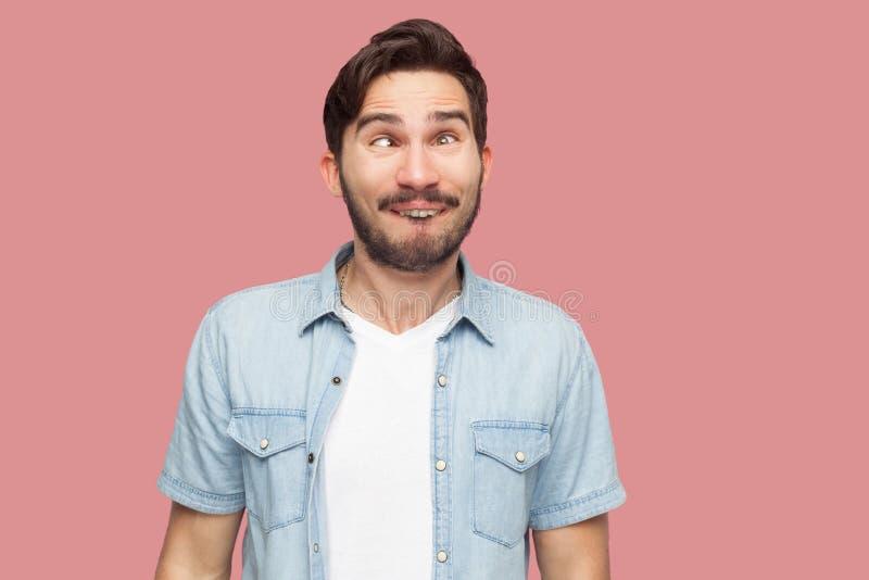 疯狂的英俊的有胡子的年轻人画象蓝色便装样式衬衣身分与内斜视和看的与滑稽的喜剧演员 免版税库存照片