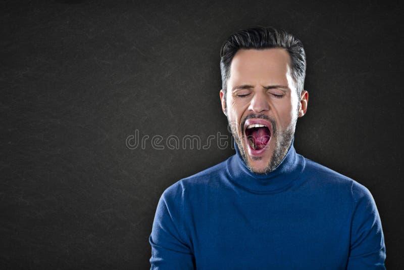 疲乏和乏味的一蓝色套头衫打呵欠的年轻人 免版税图库摄影