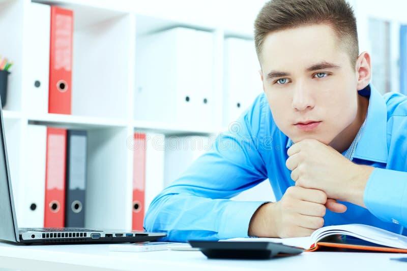 疲乏和哀伤的年轻人休息他的在他的拳头和注视着的头去,当坐他的工作地点时 免版税图库摄影