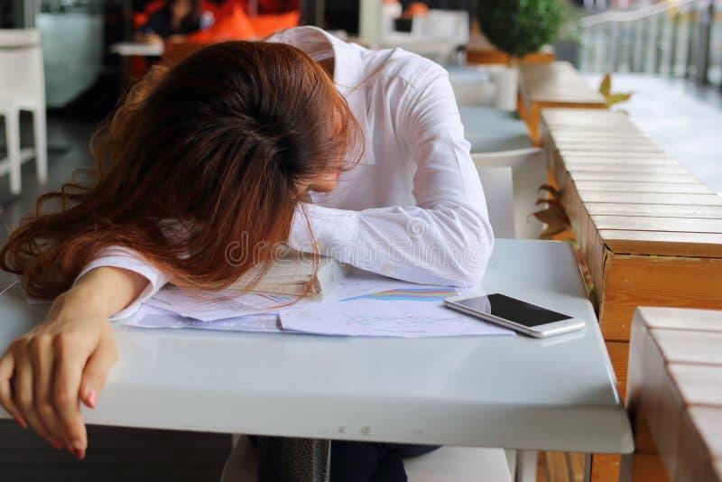 疲乏和被用尽的年轻女实业家睡眠画象在工作场所的在她的办公室 劳累过度企业概念 免版税库存照片