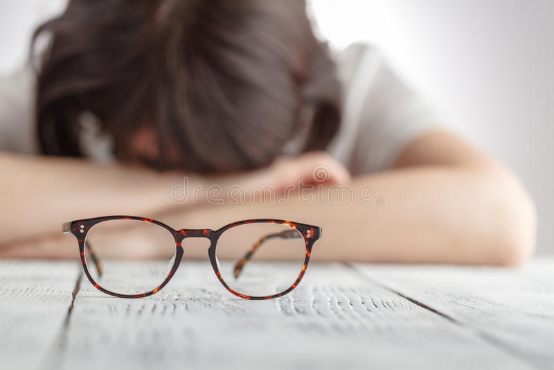 疲乏女实业家睡着在她的有眼睛gl的工作场所 免版税库存照片