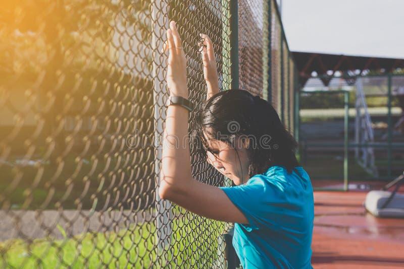 疲乏女性赛跑者跑室外和跑步在日出光 库存照片