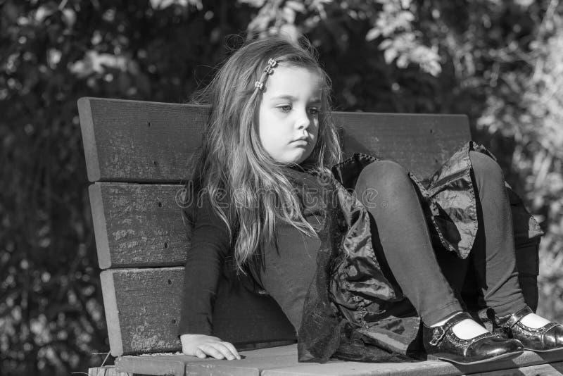 疲乏或乏味小女孩坐长凳 免版税库存照片