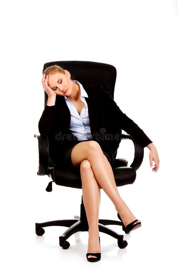 疲乏或担心的女商人坐扶手椅子 库存照片
