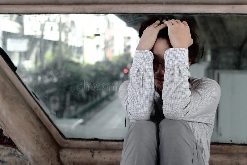 疲乏沮丧的被注重的年轻亚裔商人用在顶头感觉忧虑的手或失望对工作 免版税库存图片