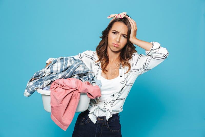 疲乏的不快乐的主妇20s运载的洗衣篮画象  免版税库存照片