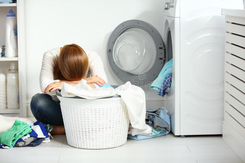 疲乏的不快乐的妇女主妇折叠穿衣入洗涤的橡皮防水布 免版税库存照片
