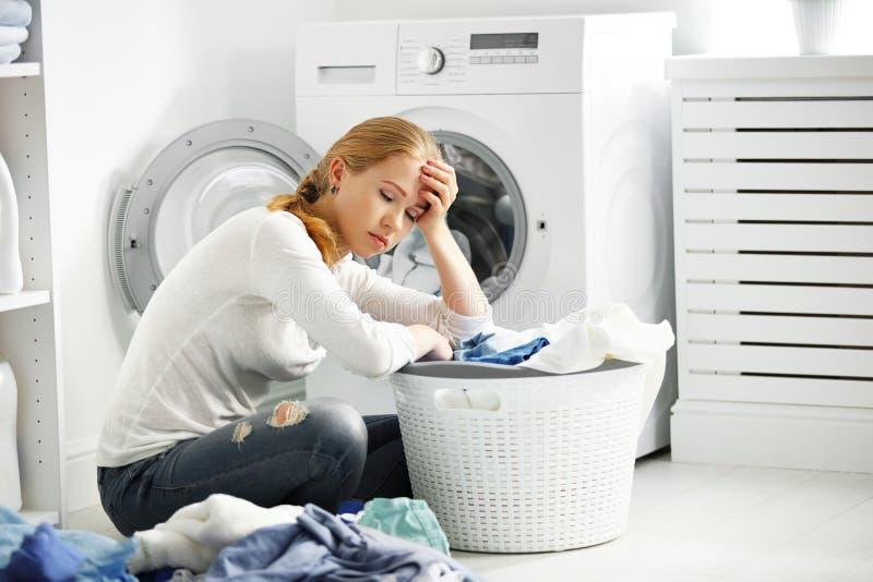 疲乏的不快乐的妇女主妇折叠穿衣入洗涤的橡皮防水布 免版税图库摄影