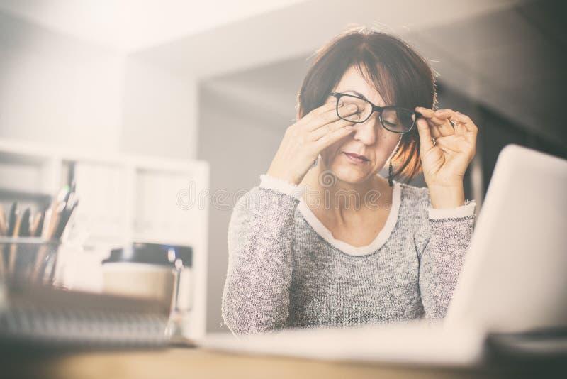 疲乏的中年妇女摩擦眼睛 库存照片