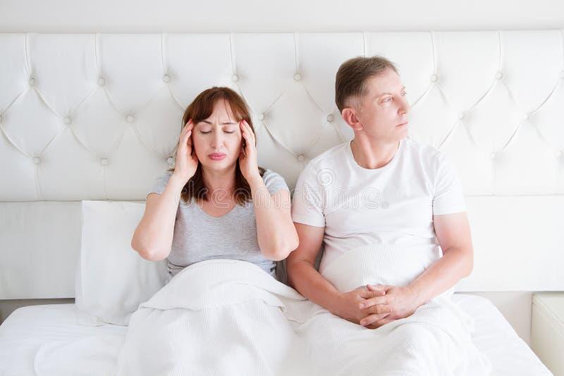 疲乏的中年家庭夫妇在床上 妇女感受痛苦和偏头痛在头 强的紧张性头疼和重音概念 复制 库存图片