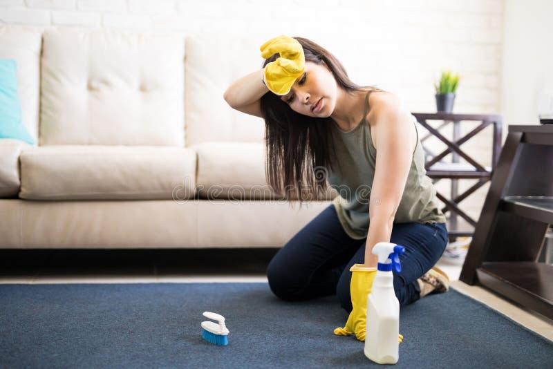 疲乏的主妇清洁地毯 免版税库存图片