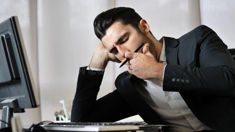 疲乏的乏味年轻商人在办公室 免版税库存图片