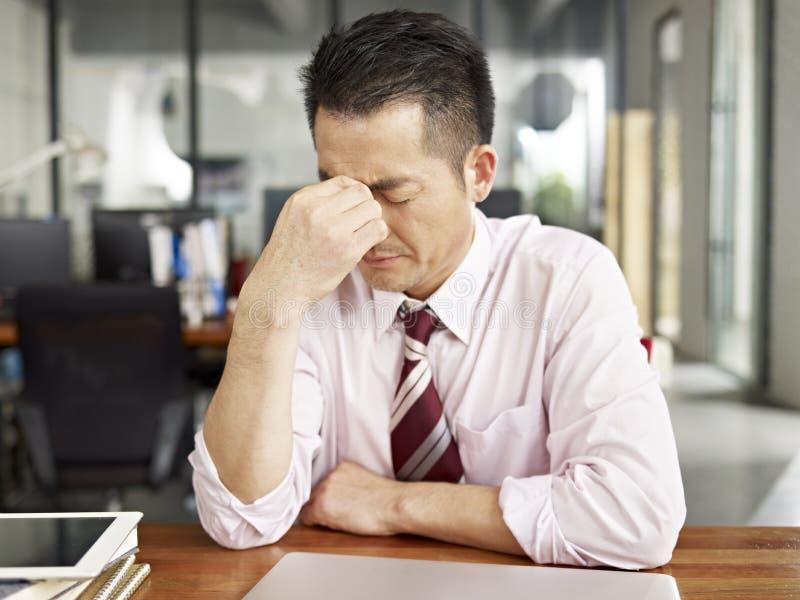 疲乏的亚裔企业人 免版税库存照片