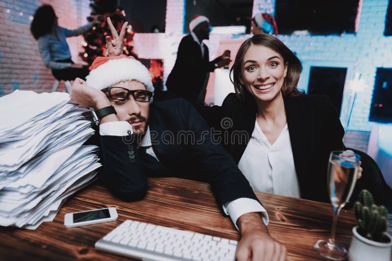 疲乏的人和愉快的女孩在办公室在除夕 免版税库存图片
