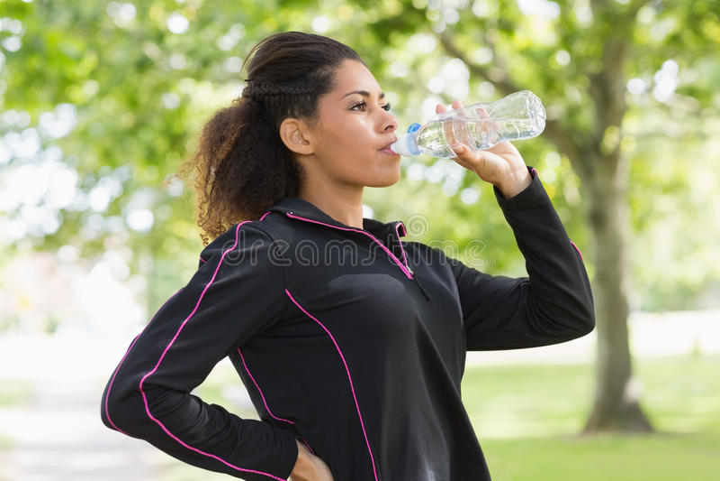 疲乏的健康妇女饮用水在公园 免版税库存图片