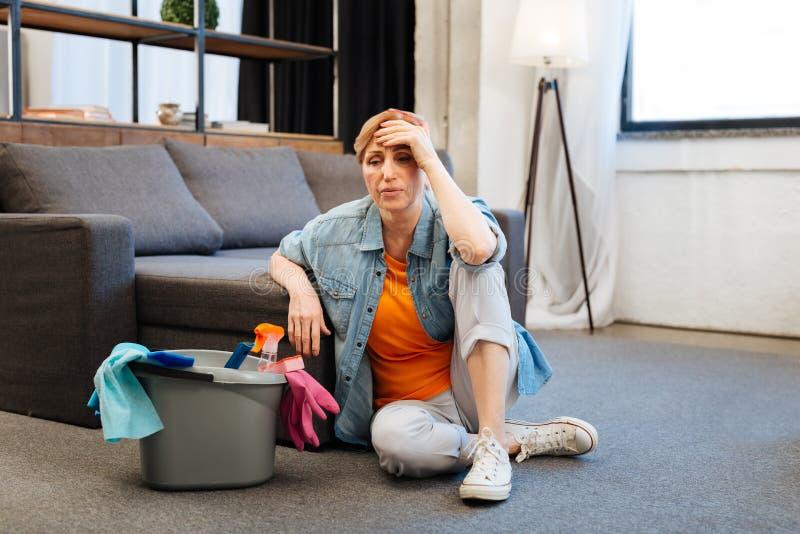 疲乏的困厄的妇女感觉病态在强烈的清洁以后 库存图片