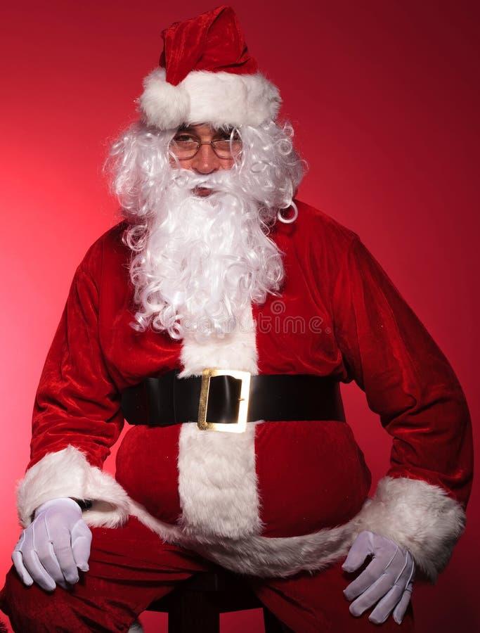 疲乏的圣诞老人通过休息坐椅子 免版税图库摄影