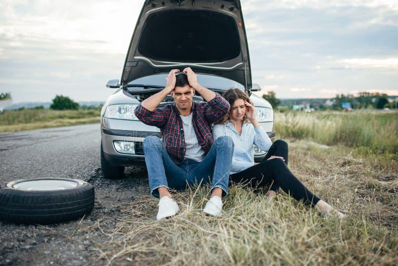 疲乏的坐反对残破的汽车的男人和妇女 免版税库存图片