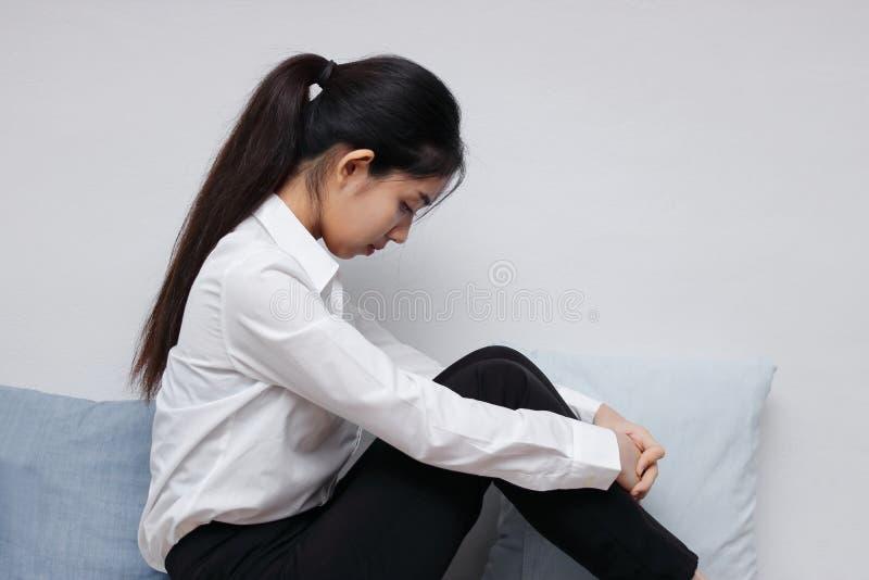 疲乏的坐在客厅的翻倒年轻亚裔妇女侧视图  库存图片