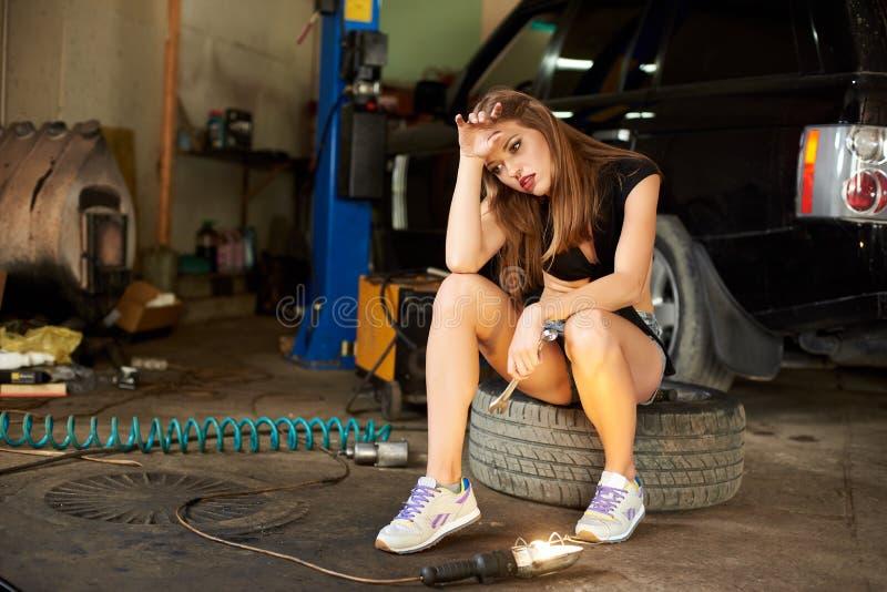 疲乏的女孩坐在车库的一个轮胎 图库摄影