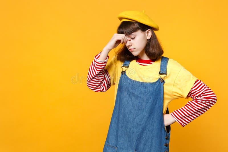 疲乏的女孩少年画象法国贝雷帽的,把手放的牛仔布sundress在鼻子上,保留眼睛关闭了隔绝  免版税库存图片