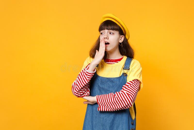 疲乏的女孩少年画象法国贝雷帽的,牛仔布sundress打呵欠,包括嘴用在黄色隔绝的手 库存图片
