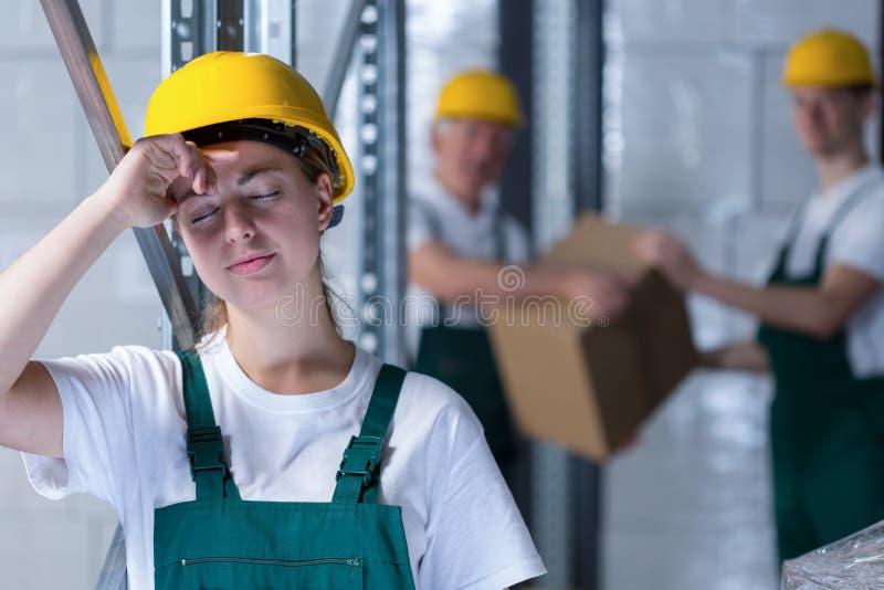 疲乏的女性工厂工人 免版税图库摄影