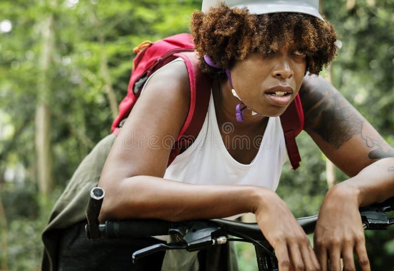 疲乏的女性骑自行车者在森林里 库存照片