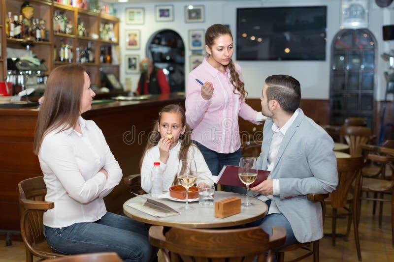 疲乏的女服务员和生气的家庭 免版税库存照片