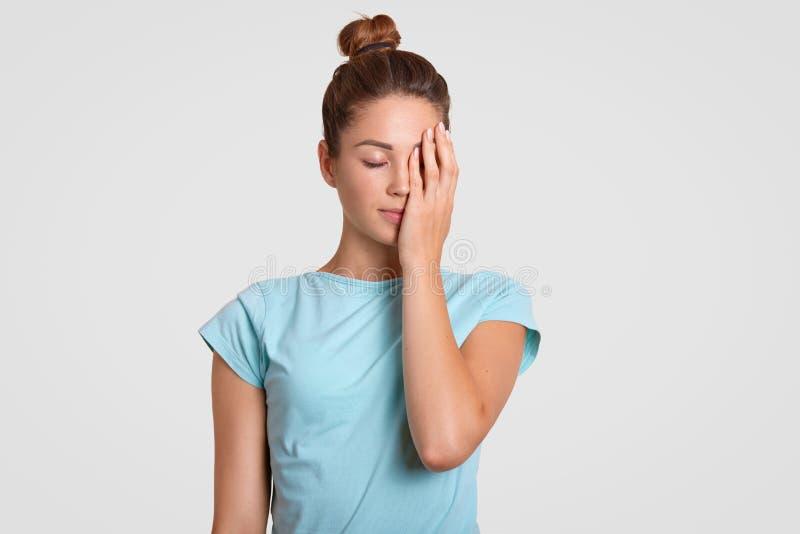 疲乏的女运动员室内射击用手盖面孔,穿戴在偶然T恤杉,保持闭上,尝试集中 女性 库存图片
