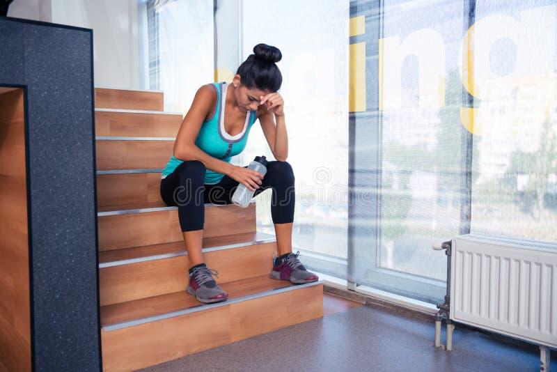 疲乏的妇女坐台阶 库存图片