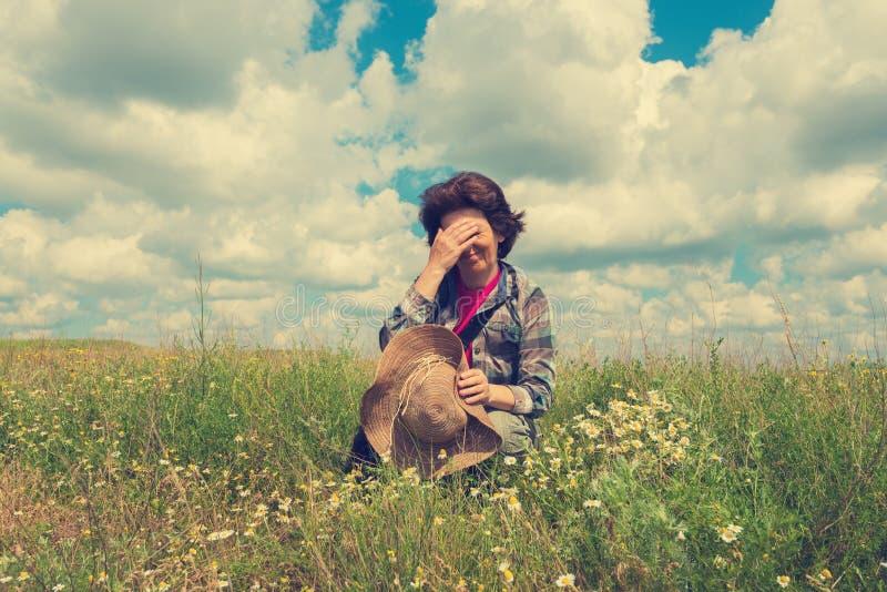 疲乏的妇女坐大草原 库存照片