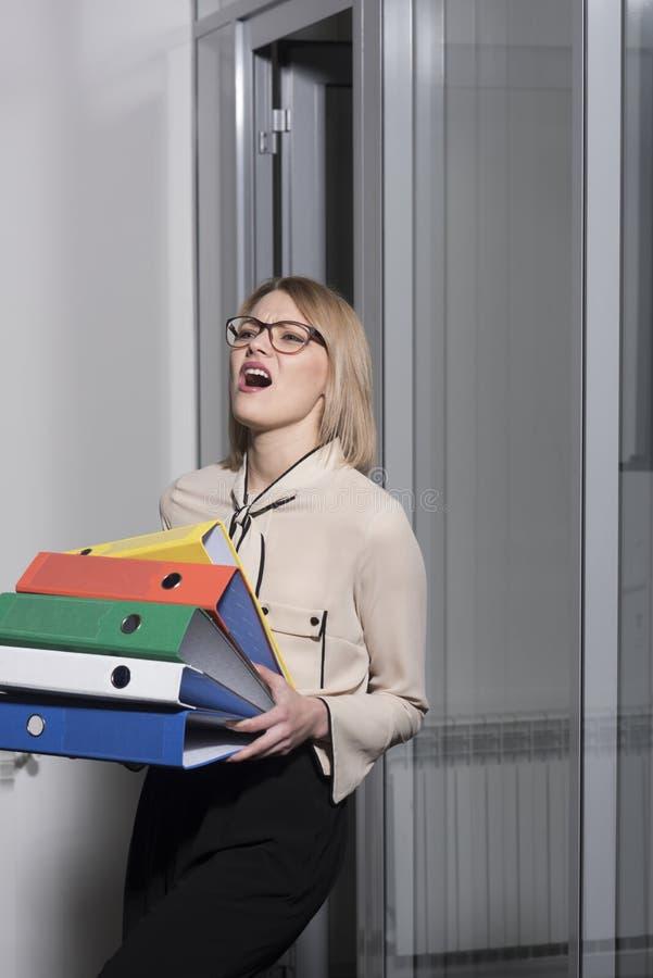 疲乏的妇女待办卷宗文件夹在办公室 与工商业票据的女商人坚苦工作 有堆的性感的秘书  免版税图库摄影