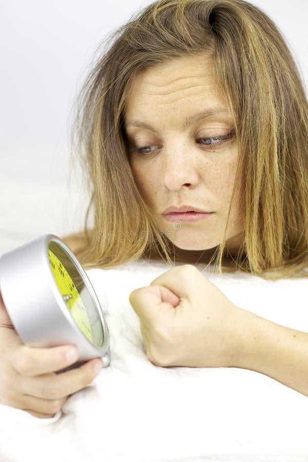 疲乏的妇女恼怒与闹钟早晨 免版税库存图片