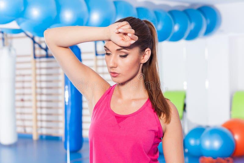 疲乏的妇女画象有休息在休息在锻炼以后 库存照片