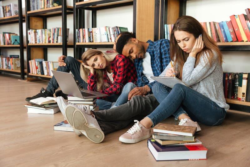 年轻疲乏的学生在图书馆里坐地板 库存图片